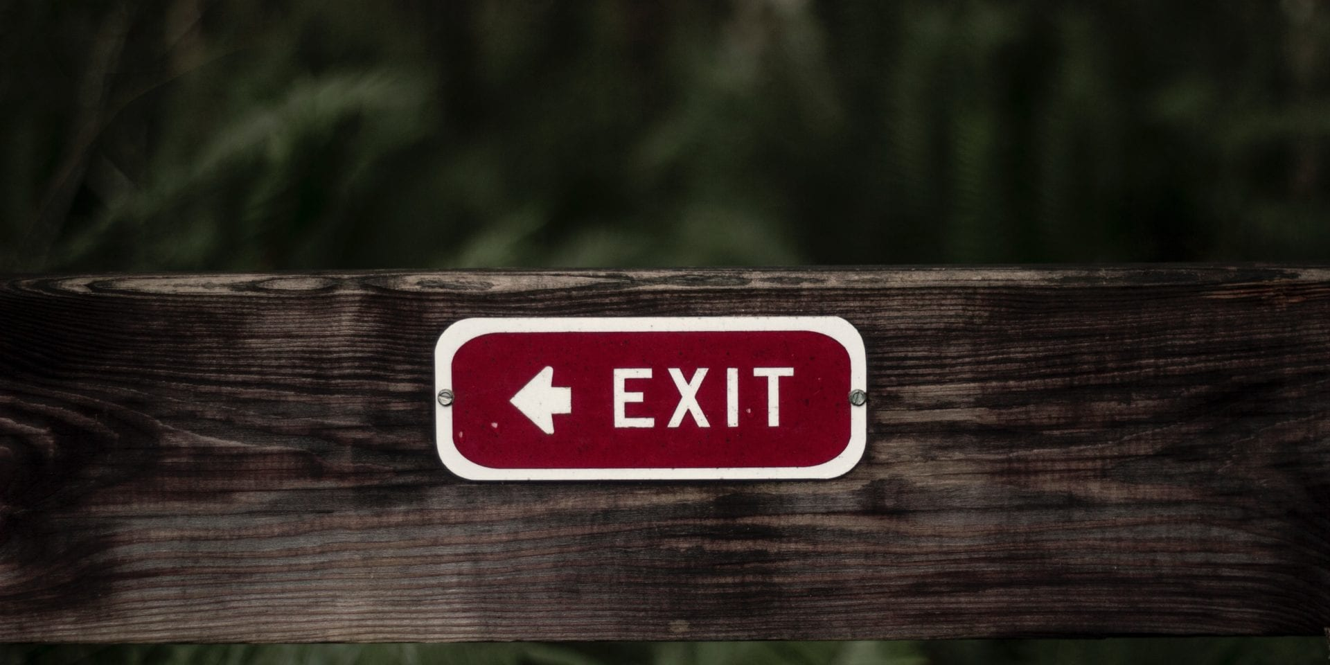 Employee retention rate – red exit sign on a wooden fence showing challenges in attracting and retaining employees
