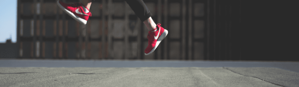 How to raise your professional profile - person in red shoes jumping in front of a block of flats