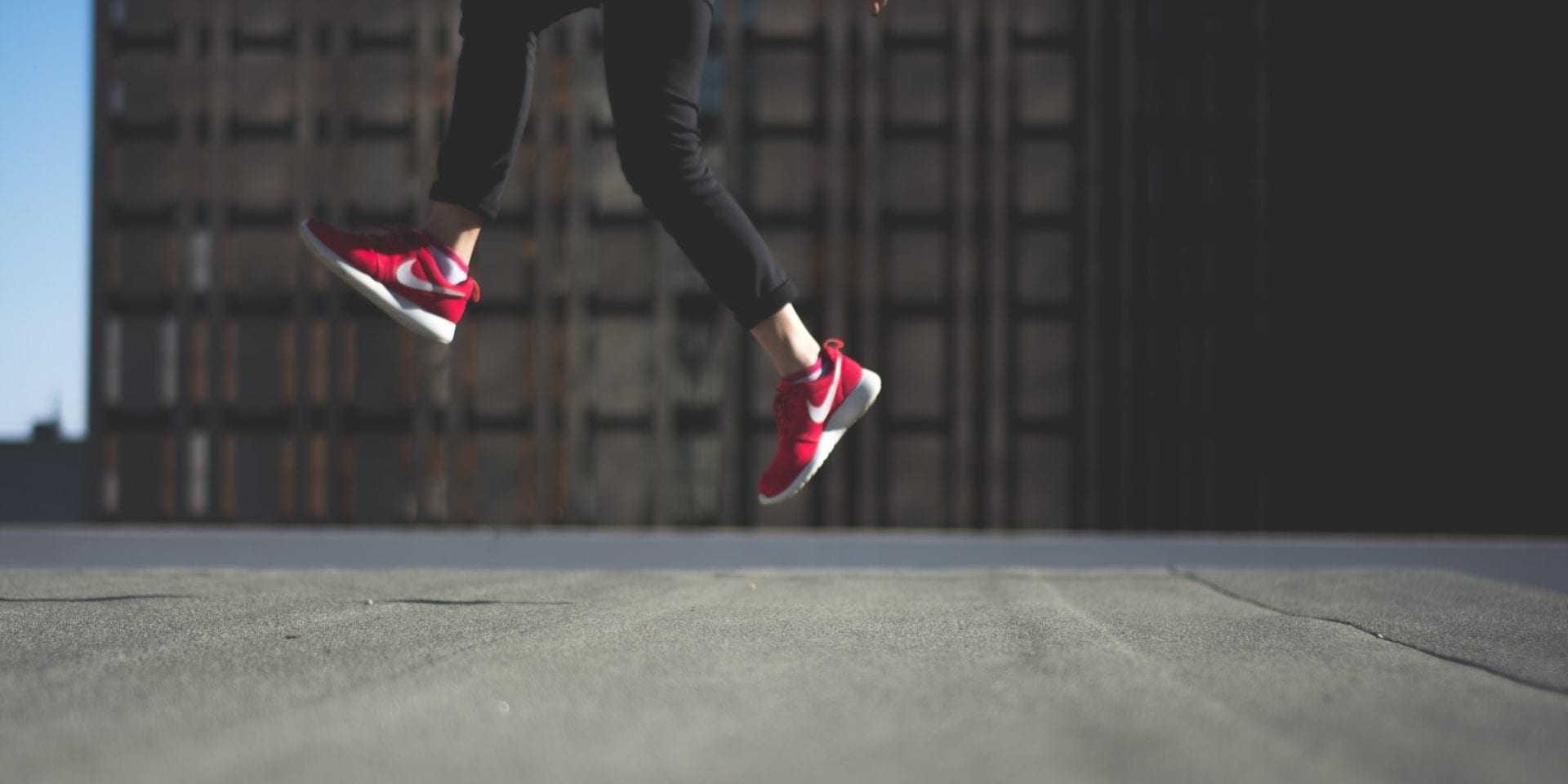 How to raise your profile at work: person wearing red Nike trainers jumping in front of a building