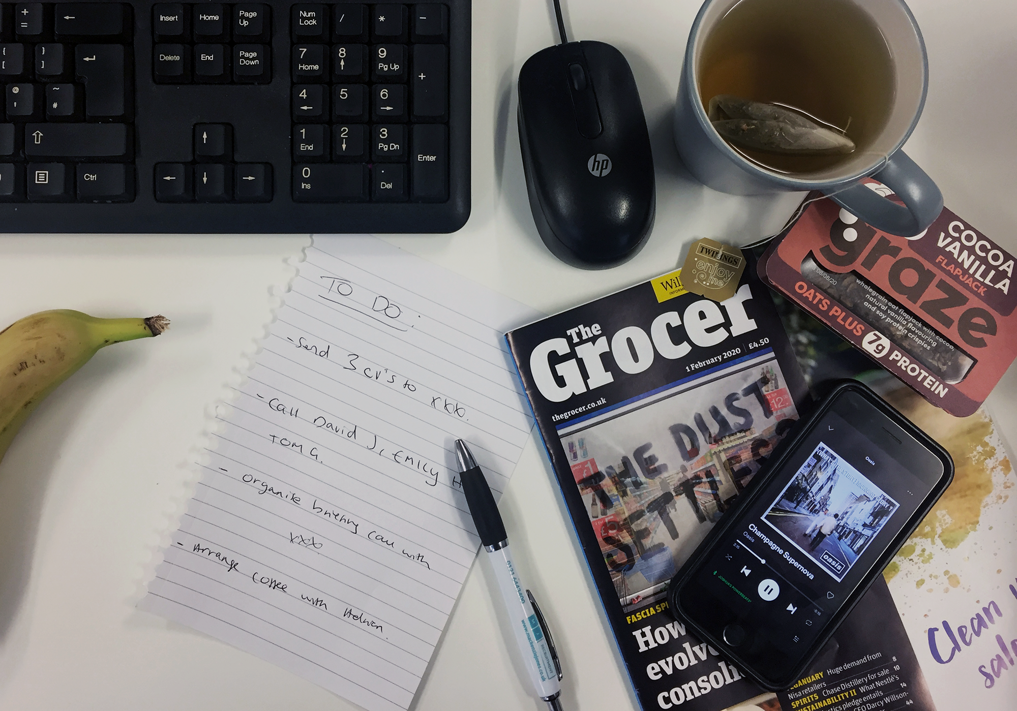 aerial shot of a desk featuring The Grocer Magazine, Twinings tea, graze protein flapjack and phone showing Oasis playing on Spotify
