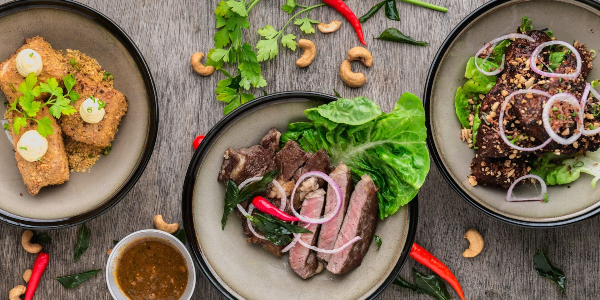 Three plates of meat dishes with salad, creative food jobs