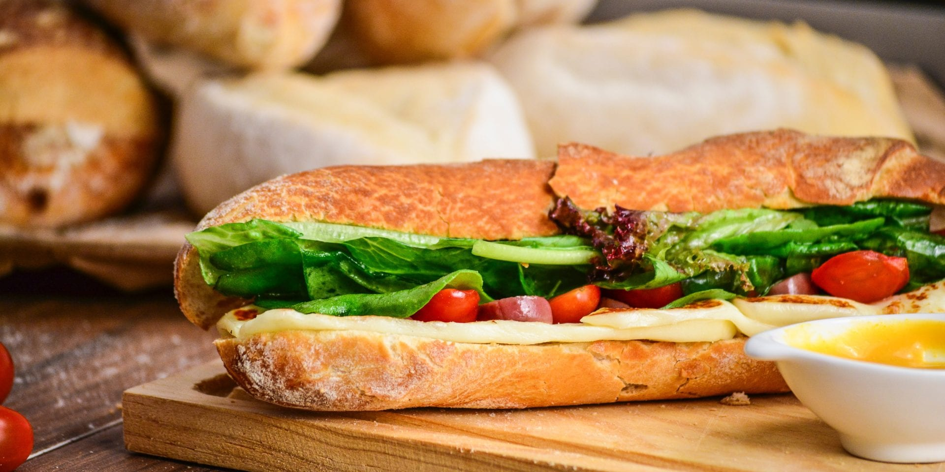 A salad filled baguette on a wooden chopping board – our case study for Adelie Foods careers