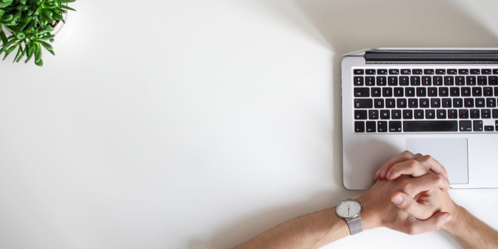 Top five video interview tips: Hands clasped together on top of open laptop